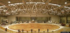 The World's Largest Pizza Is Ginormous. Last week, five Italian chefs came together to create the World's Biggest Pizza. The delicious monstrosity measured 131-feet in diameter, tipped the scales at over 51,000 pounds, and contained 1,488 pounds of margarine, 19,800 pounds of flour, 10,000 pounds of tomato sauce, 8,800 pounds of mozzarella cheese, 551 pounds of salt, 220 pounds of lettuce and 55 pounds of vinegar.