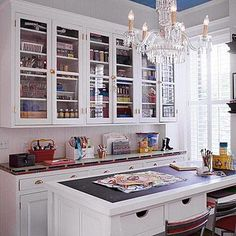A central island welcomes artists with a broad work space and plenty of storage in undercounter drawers. Topped with dark slate, the island provides a desklike area that is easily cleaned and can function as a chalkboard. The island and hutch provide handy organization. Glass cabinet doors keep supplies in view, making selection quick and order uncomplicated. The hutch's long line of cabinets and drawers delivers plenty of storage and conceals large bins of materials.