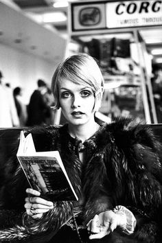 Twiggy reading a guide book to Tokyo at London Airport before departing for Japan, where she will be modelling a fashion collection, 1967