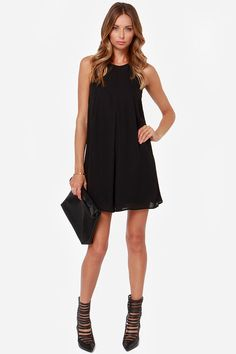 """Go for a classic look with contemporary flair in the Modern Audrey Black Dress! Light woven material flows from a chic high rounded neckline and sleeveless bodice boasting delicate darting detail atop a flirty A-line cut. A small keyhole opening can be found at back below a looping button closure. Lined in a stretch knit. Model is 5'9"""" and is wearing a size small. 100% Polyester. Hand Wash Cold."""