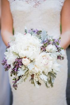 a bouquet of white peonies, purple waxflowers, gray dusty miller, blue succulents, ivory spray roses, and blue tweedia