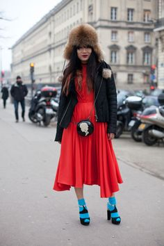 Paris Street Style Couture 2013.  A red dress, black parka, turquoise ankle socks, fox fur trapper hat, and LULU GUINNESS round cameo purse.