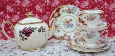 Vintage bone china tea for two set made by English china company Tuscan, with teapot made by Sadler, likely manufacture date 1940s, possibly older. The teapot is full sized cube shape. The teapot has an ivory background decorated with a design of a spray of roses in dark red. The teapot is further enhanced with rich gilding to the spout, handle and top rim. The gilding is bright but has a little age related rubbing. The teapot is in good condition free from chips, cracks, staining but there…