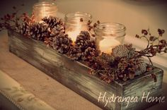 Perfect rustic planter - wooden box with distressed finish, pinecones and bare branches with berries, and plain mason jars with candles inside ... lovely rustic table decor for fall to winter