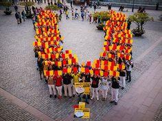 """La 'V' arriba a Estocolm - elsingular.cat, 15/08/2014. A la concentració es van poder sentir crits d'independència i a l'acabar es va cantar 'Els Segadors'. A més, es va formar la 'V' recreant la senyera. En el vídeo, realitzat per Marçal Morell, es pot veure com un dels participants explica que """"avui hem organitzat una V humana per demanar el dret a decidir el nostre futur. Que ens deixin votar, si us plau""""."""