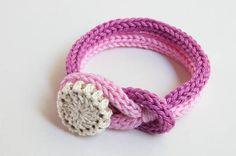 Handgebreide armband in roze met handgemaakte knoop.