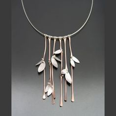 """Gold filled stalks of bamboo and sterling leaves shimmer on this stunning statement piece. If you like lots of movement and a little bit of unpredictability, this necklace is for you! The hinged, hammered stems measure 3"""" in length and total width of the pendant area equals approximately 2 1/2 inches. Strung on a 16"""" sterling silver cable wire and finished with a lobster clasp and 2"""" extender."""