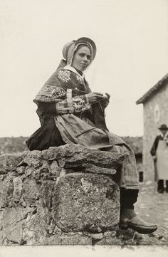 A young woman of Auvergne sits on a stone ledge and knits. #Auvergne