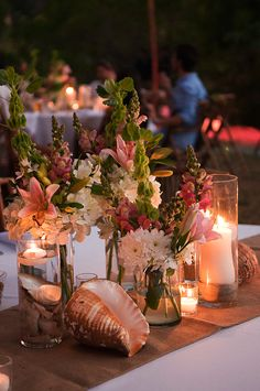 beach wedding centerpiece - obvi with less flowers, and more fishbowl looking vases