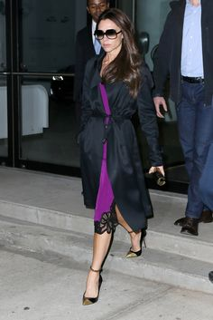 Victoria Beckham wears a black satin topper from her pre-fall collection and a purple dress with lace hem