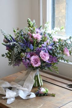 Lilac and blue spring bridal bouquet. Hyacinths, muscari, freesias.