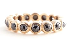 Black, rose-cut diamonds dance around a band of gold.