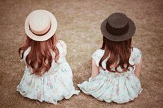 草原に座って景色を見ている双子の女の子たち