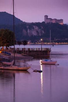 Lakefront view with La Rocca fortress in Angera at dusk, Arona, Lake Maggiore, Piedmont, Italy