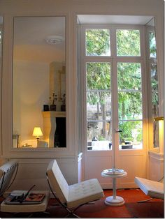 Paris hotel:  love the white + red; French doors; white leather chairs