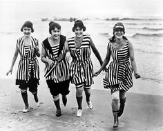 Four young women in matching beach wear run out of the surf in Los Angeles, California in 1910. By the early 20th century women still wore knickers under their bathing suits, but revealed a little more leg.