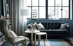 Soggiorno con divano a 2 posti in pelle nera, poltrona con cuscino beige e struttura in betulla, set di tavolini in impiallacciatura di betulla.