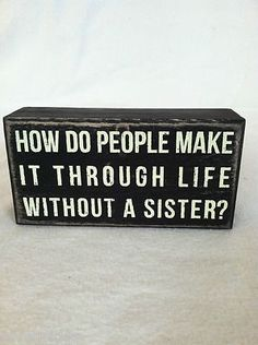"""Black wooden box sign. """"How do people make it through life without a sister?"""""""