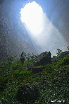 Sunlight touches the plants inside a sinkhole in the mountainous Xuanen County in central China's Hubei Province, May 19, 2015. Due to the local Karst landscape and humid climate, a sinkhole more than 290 meters deep in Xuanen has become home for various plants and animals. A full and original eco-system is kept in the hole as it is hard for human to get in. (Photo: Xinhua/Song Wen)