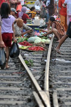 Food hawkers ply their wares on the railroad tracks in Surabaya, East Java, on June 23, 2012. The vendors have refused to follow  government order to move to a safer but more remote location. The sellers say they prefer trading on the tracks because they are closer to their train-bound customers. (Antara Photo/M Risyal Hidayat)