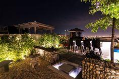 terrasse moderne avec coin repas, pergola et fontaine en cascade gabion