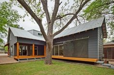 """This simple and efficient vernacular form opens to the private yard with a framed view of an old growth tree. A large hung sliding """"barn"""" door opens the entire wall and living space up to the view and connects to the adjacent porch providing a covered place to sit. This house achieves very big ideas on a budget.    Stuart Sampley Architect  Moontower Residence"""