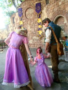 Little girl walking with Rapunzel and Flynn Ryder.