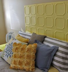 This DIY headboard project was created using styrofoam ceiling tiles, spray painted yellow, and attached to the wall with sticky adhesive squares.