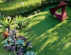O gramado  exibe umma escultura de Amilcar de Castro (1920-2002), bromélias-imperiais (Vriesea imperialis) (1) e triális (Thryallis glauca) (2).