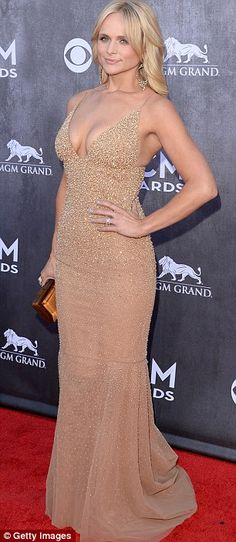 Strike a pose: The 30-year-old bombshell donned a plunging champagne-coloured fishtail gown
