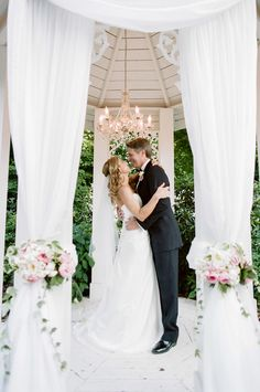 """""""Picture Window"""" draping on the pavilion with floral tie backs by @flwrgirlcaprice. A little chandelier is just enough sparkler to make this an even lovelier backdrop for a garden wedding ceremony.   CJ's Off the Square 