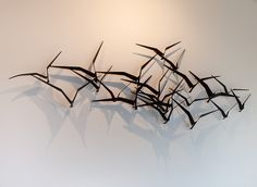 C. Jere iron wall sculpture is made from iron and casts a dramatic shadow of birds in flight.