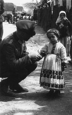 German soldier greets little Russian girl. I think she's so beautiful