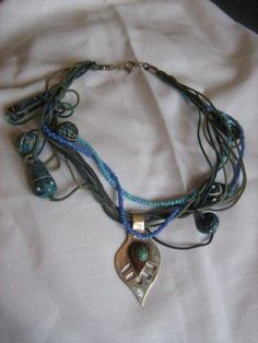 Organic peacock feather pendant with blue wood beaded necklace.