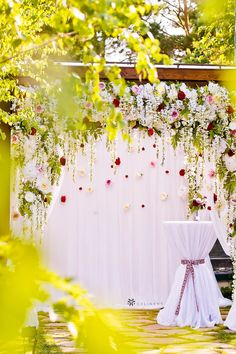 Outdoor wedding draping backdrop design for summer wedding ceremony decorations from CV Linens. Click to shop our wedding linens and backdrop drape curtains on a budget. Gorgeous outdoor wedding backdrop design with flowers and greenery decorations. Wedding cocktail table decorations under wedding arch backdrop set up for cocktail hour or guest book sign up. Summer wedding decorations for wedding arch backdrop design with flowers and greenery garlands. Outdoor Wedding Backdrops, Wedding Draping, Wedding Backdrop Design, Wedding Reception Backdrop, Wedding Linens, Wedding Ceremony, Wedding Flowers, Summer Wedding Decorations, Ceremony Decorations