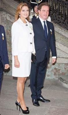 Princess Madeleine of Sweden wears a matching white suit with bow buttons, a black clutch and black heels.