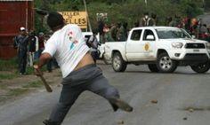 Un hombre arroja piedras contra miembros de la fuerza policial de la comunidad - que se oponen a las elecciones - en Tixtla en el estado de Guerrero.