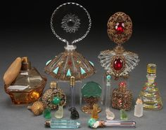 EIGHT CZECH PERFUME BOTTLES, EARLY 20TH CENTURY. Of various form including a ruby jeweled and gilt filigree, a cut glass gilt filigree and turquoise mounted vase with large rosette form cut stopper, several Nailsea type including a painted porcelain stopper with bust of a flapper girl together with six miniature satin glass animal figures. The largest 6.25 inches (15.5 cm).