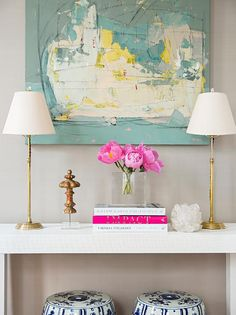 Resplendent yellow and blue foyers boasts light gray walls framing a yellow and blue abstract painting flanked by thin brass table lamps positioned atop a white lacquered console table also holding a white quartz votive and pink peonies in a square glass vase sat on stacked white and pink books while under the table two white and blue stools are placed side by side.