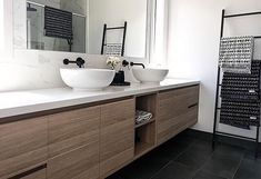 Wall hung timber veneer vanity with drawers and doors, double above counter vessel basins, matte black wall spout and wall mixer, matte black ladder towel rail. Carrara marble splash back wall. Project by - @lotnine08interiors #taps #interiordesign #bathroom #australia #architecture #bathroomdesign #bathroomcollective Visit our website for more www.bathroomcollective.com.au