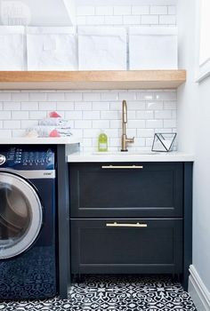 Awesome laundry room with patterned tile floor, subway tile and floating shelves.