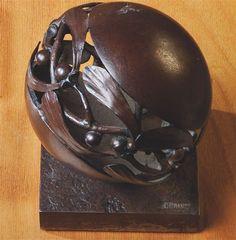 EDGAR BRANDT (1880-1960) PRESSE-PAPIER, 1921 En fer forgé patiné brun, de forme sphérique à décor ajouré de gui stylisé, reposant sur une base carrée Hauteur : 10 cm. (3 7/8 in.) Estampillé E BRANDT sur la base