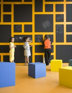 This eye-catching wall has individual boards for children. Boards are movable. Dramatic against the yellow wall.