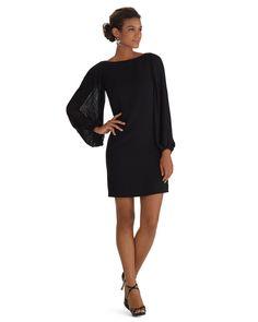 Chiffon sleeves on a little black  crepe dress fall open in pliss