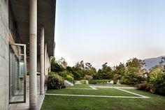 Las terrazas están protegidas por un alero asimétrico que se proyecta desde un conjunto de esbeltas columnas de concreto.