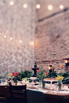 this is one of my favorite ideas with the old brick and clay in the back, the white christmas lights, the flowers and accenting shades and colors - this is one my favorites for ceremony and/or reception