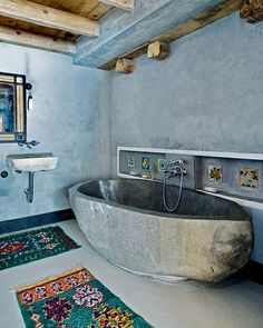 Awesome bathtub. Love the rendered concrete wall too and the wooden ceiling.