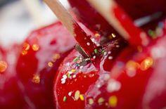 Kandierter Apfel: Die Holzstäbchen in einen Apfel stecken. 4 EL Zucker gleichmäßig auf einem Backblech (zum Abtropfen). Zucker, Wasser, Speisefarbe und Essig in einen Edelstahltopf mit dickem Boden geben und schnell aufkochen lassen. Kochen lassen, bis ca.150 C. Topf sofort vom Herd nehmen und die Äpfel nacheinander hineintauchen und drehen, bis sie völlig mit dem Zuckersirup überzogen sind. Kopfüber auf das vorbereitete Backblech setzen und abkühlen lassen.