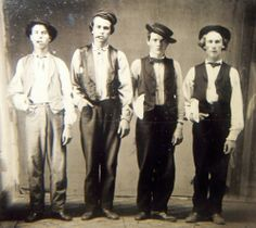 "a tintype of (allegedly) Billy the Kid, Doc Holliday, Jesse James, Charlie Bowdre.  Doc Holliday is wearing a badge, the other three have white-handkercheifs attesting they are ""peace officers.""  #signsAndSymbols"