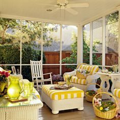 A classic southern porch. The white rocker and wicker furniture paired with the yellow fabric is bright and inviting.  I like the chunky wicker.